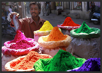 A merchant measures out dye for sale during the festival