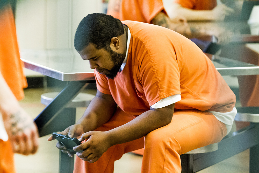 Instead of spending hours watching daytime television, this inmate comletes an educational lesson on an Edovo tablet.