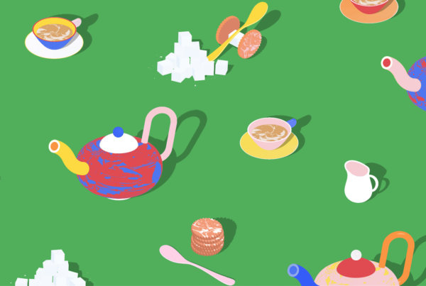 Colorful teapots and sugar cubes arranged on a green background
